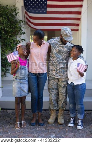 Smiling african american soldier father hugging wife and children in front of house. soldier returning home to family.