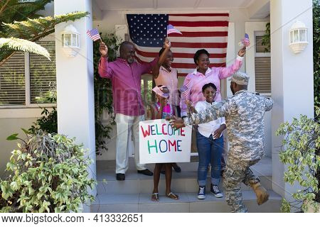 African american soldier father greeting his happy three generation family outside house. soldier returning home to family.