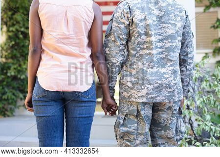 Midsection of african american male soldier and wife standing holding hands in front of their house. soldier returning home to family.
