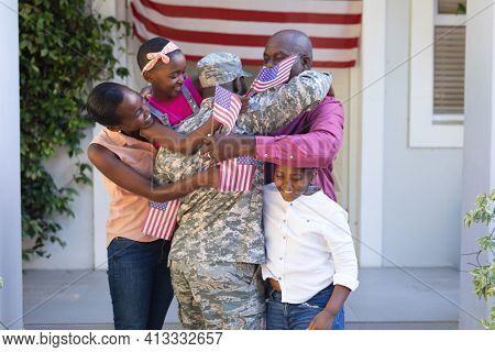 African american soldier father hugging wife, children and father in front of the house. soldier returning home to family.