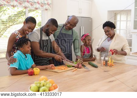Happy african american parents cooking with son and daughter and grandparents in the kitchen. three generation family spending quality time together.