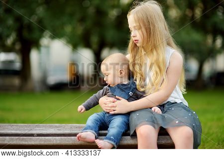 Cute Big Sister Admiring Her Baby Brother. Adorable Preteen Girl Holding Her New Baby Boy Brother. K
