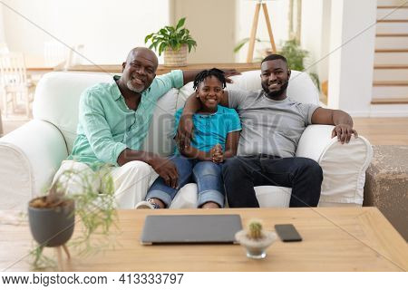 Portrait of senior african american fon couch smiling with adult son and grandson embracing. happy three generation family spending time together at home.