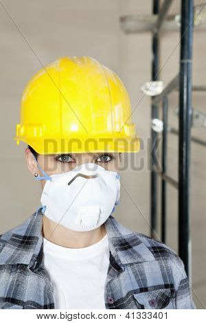 Portrait of woman worker wearing dust mask at construction site