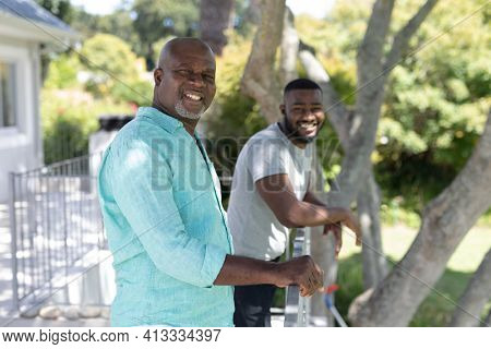 Portrait of smiling senior african american father and adult son standing on terrace in sunny garden. happy family spending time together at home.
