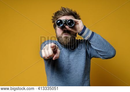 Bizarre Shaggy, Bearded Man In A Knitted Sweater Looks Through Binoculars, He Saw Something And Poin