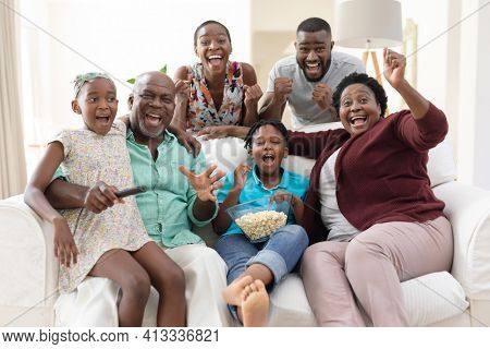 Excited african american parents, grandparents and grandchildren on couch watching tv and cheering. happy three generation family spending time together at home.