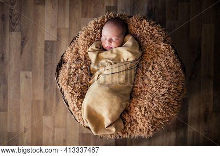 sleepy newborn baby lying on fluffy soft rug  in basket