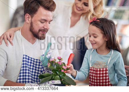 A little girl helping her father to plant a flowers in a family atmosphere at home. Family, home, playtime