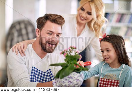 A young parents enjoying their daughter help while they planting the flowers in a family atmosphere at home. Family, home, playtime
