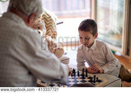 A little grandson enjoy playing a chess game with his grandpa in a relaxed atmosphere at home. Family, home, playtime
