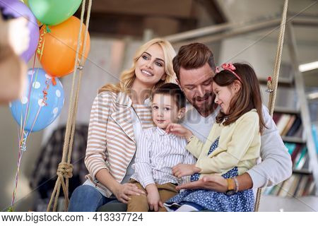 A young lovely family sitting on the swing in a relaxed atmosphere at home together and posing for a photo. Family, home, playtime