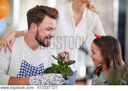 A happy father and his little daughter planting flowers in a family atmosphere at home together. Family, home, playtime