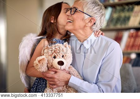 A little girl and her grandma are full of emotions while spending time in a family atmosphere at home together. Family, home, love, playtime