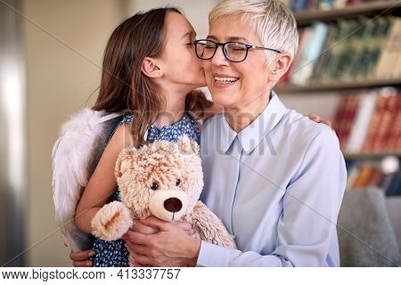 A happy grandma enjoys kisses and emotions getting from her little granddaughter in a family atmosphere at home. Family, home, love, playtime