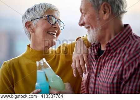 A happy elderly couple enjoying a drink and time spending together in a cheerful atmosphere. Spouses, elderly, together