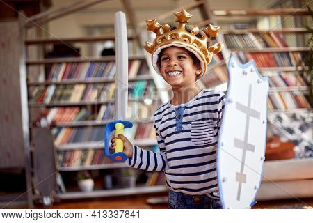 A cute little boy dressed as knight is posing for a photo while playing in a relaxed atmosphere at home. Family, home, playtime
