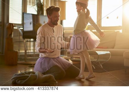 A little ballerina practicing a ballet move at a training in a relaxed atmosphere at home with a support of her father. Family, ballet, training