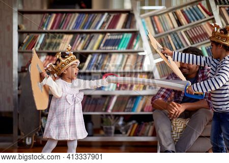 Children dressed like knights are enjoying swords fight game while spending a playtime with their parents in a cheerful atmosphere at home. Family, home, playtime