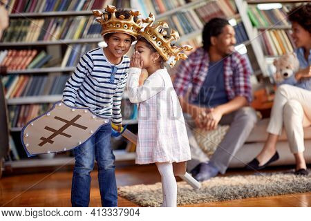 Children dressed as knights whisper and murmur while playing with their parents in a family atmosphere at home. Family, home, playtime
