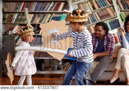 Children dressed like knights are fighting with swords while being watched with their parents in a playful atmosphere at home. Family, home, playtime