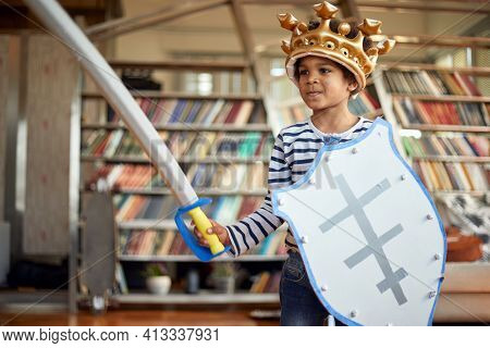 A cheerful little boy posing with a sword and a shield while playing in a relaxed atmosphere at home. Family, home, playtime