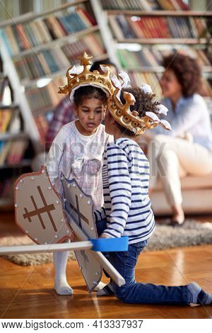 Children dressed as knights whisper and murmur some secrets while playing in a relaxed atmosphere at home with their family. Family, home, playtime
