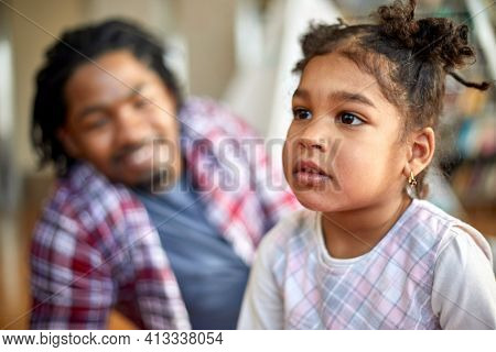 A cute little girl is posing for a photo while playing with her father in a relaxed atmosphere at home. Family, home, playtime