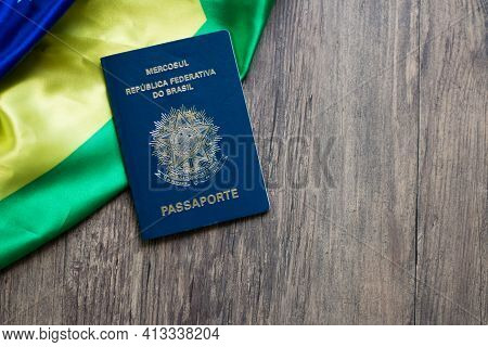 Brazilian Passport On Wooden Table And Brazilian Flag Top View.