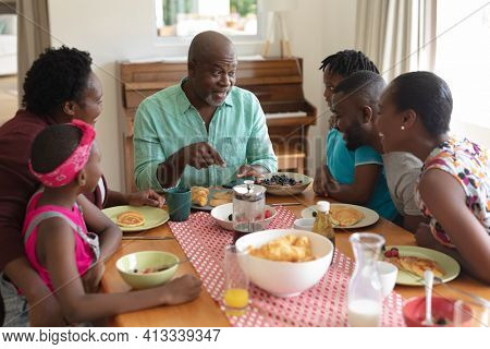 Happy african american grandfather talking with grandchildren and their parents at family meal. three generation family spending quality time together.