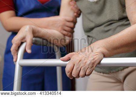 Elderly Asian Woman Using A Walker At Home With Daughter Take Care