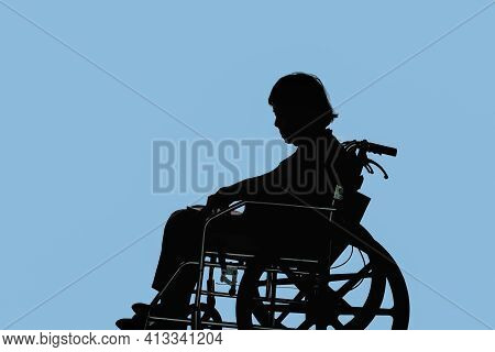 Silhouette Of Disabled And Dejected Elderly Woman Sitting In Her Wheelchair