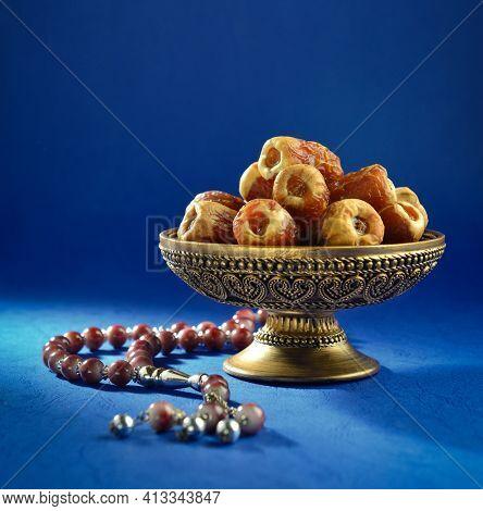 An ornamental bowl of dates with islamic prayer beads. 'Ramadan Kareem' stock photo of dates.