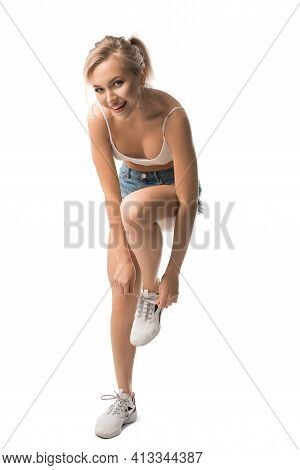 Cheerful Young Woman Tying Shoelaces On Sneakers