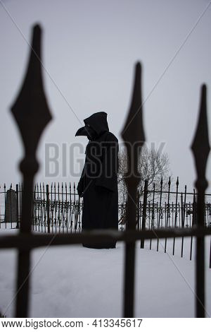 Medieval Plague Doctor Stands On Winter Graveyard Near Metal Fence