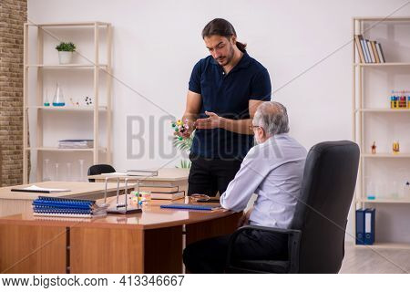 Old male teacher physicist and young male student in the classro