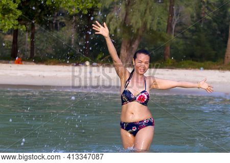 Woman In Bikini Pretty Is Play Water At Beach Koh Chang Thailand. Koh Chang Is Located In The Easter