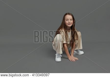 Studio Portrait Of A Young Girl With Brown Hair, With Long Hair, On A Gray Background