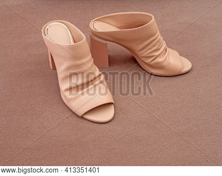 Beige High Heeled High Heeled Mules On Grey Background.