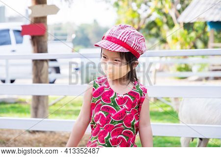 Cute Asian Girl Wearing Orange Cloth Face Mask. Child Visit Zoo During The Coronavirus Outbreak. Pre