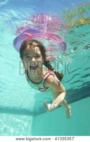 Portrait of a happy preadolescent girl swimming underwater