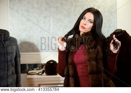 Luxury Clothing Concept. Woman With Fur Coat. Girl In A Fur Coat Coat In Shop With Fur On Background