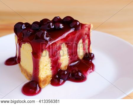 Slice Of Baked Cheesecake Topped With Mouthwatering Blueberry Sauce On Wooden Table