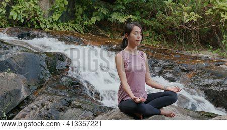 Sport woman do yoga at waterfall