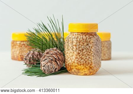 Pine Nut With Honey In A Transparent Jar With A Yellow Lid. Nearby Are Pine Cones And Needles. In Th