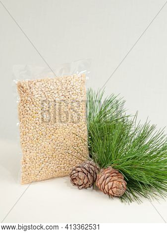 Peeled Pine Nut Kernel. Vacuum Packed. On A White Background. Nearby Pine Nuts And Cones.