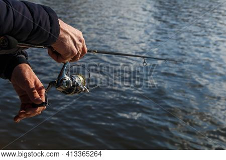 Fishing On The Lake At Sunset. Fisherman With Rod, Spinning Reel On The River Bank. Sunrise. Fishing
