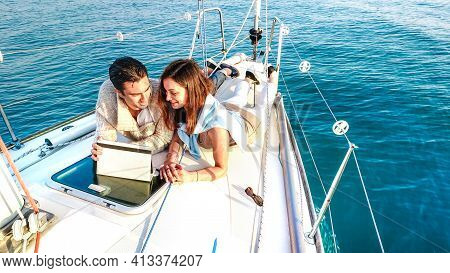 Young Couple In Love Having Fun With Tablet Pc On Sailboat - Luxury Travel Life Style And Digital No