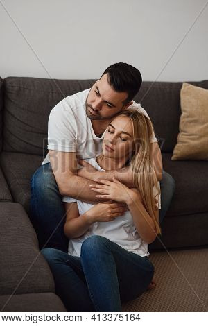 Man And Woman In Love Relaxing At Home. Young Couple. Husband Cuddles His Wife