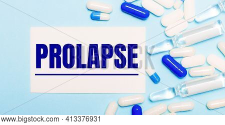 Pills, Ampoules And A White Card With The Text Prolapse On A Light Blue Background. Medical Concept